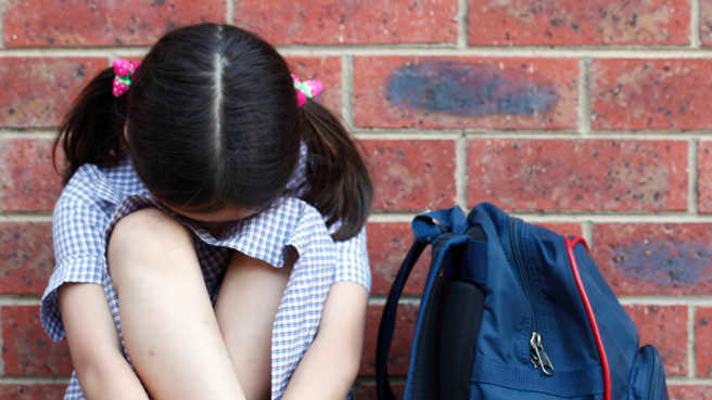 upset girl head down outside of school
