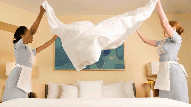 two maids lifting a bedsheet
