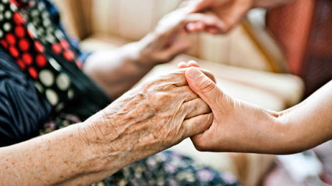 elderly woman holding hands with child