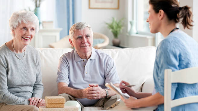 nurse talking with elderly couple