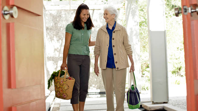 woman and senior walking down hallway