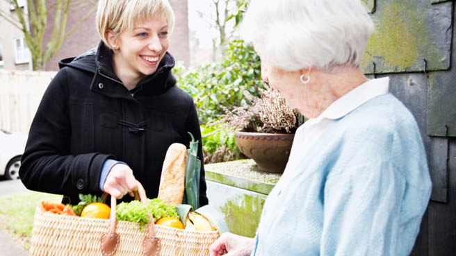 woman helping senior carry groceries