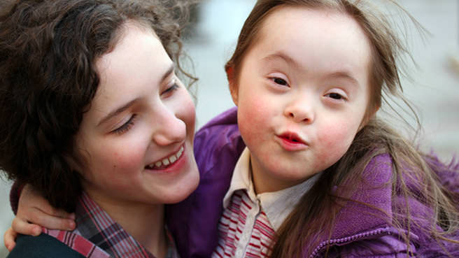 woman holding special needs girl