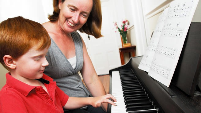 woman teaching little boy piano