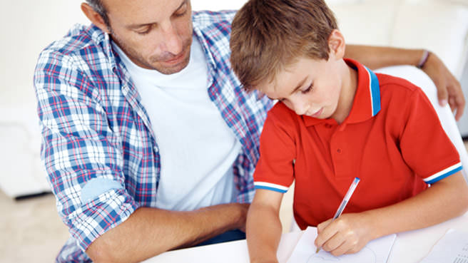 man helping little boy with homework