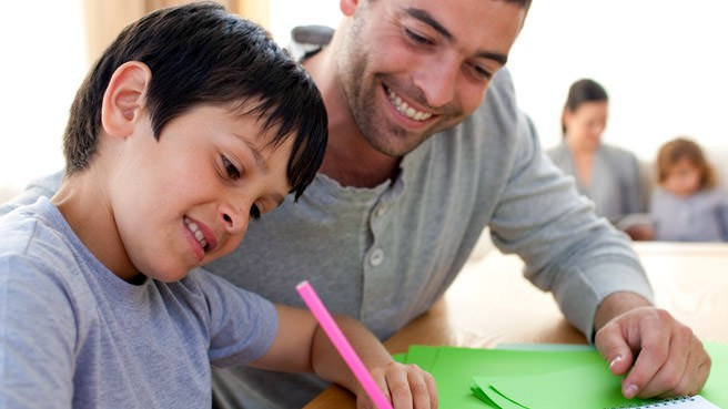 tutor and boy smiling at work